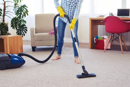 Pretty female cleaning with vacuum cleaner carpet