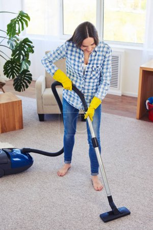 Gorgeous woman cleaning with vacuum cleaner carpet