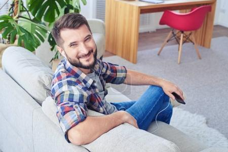 Appealing man listening to music with headphones and smiling