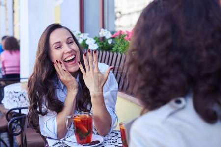 Delightful bride showing wedding ring to friend