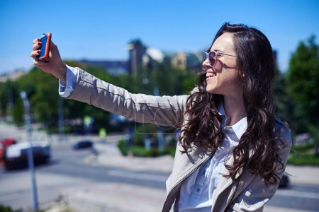 Lady taking selfie in front of city panorama