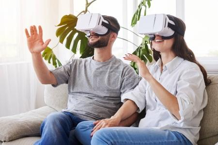 Couple in VR glasses holding hands and orienting in space