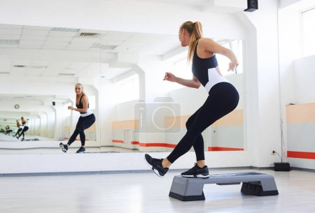Photo for Back view of sporty athlete having a step aerobics in a gym. Woman doing corner knee step - Royalty Free Image