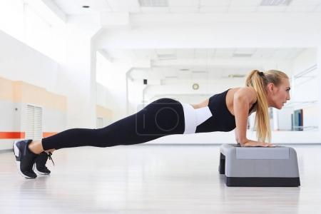 Strong female doing push up abdominals workout posture