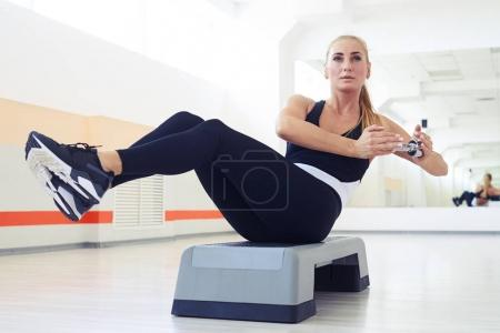 Muscular woman with slim fitness body doing exercises with dumbb