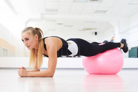 Young woman doing stretching plank on fitball