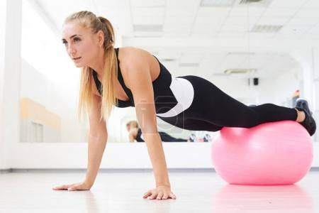 Woman doing pilates exercises with pink fitball in gym