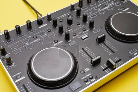 Well-equipped DJ panel on yellow background, flat lay