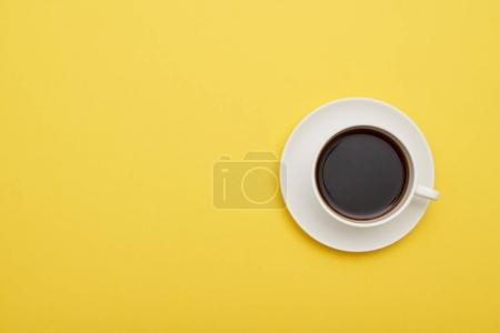 Flat lay of yellow desk with cup of aromatic coffee