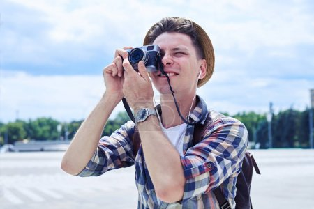 Traveler hipster young man takes photographs with vintage photo