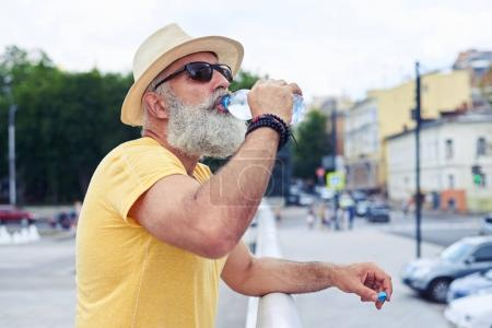 Senior man drinking water from a plastic bottle with an urban ci