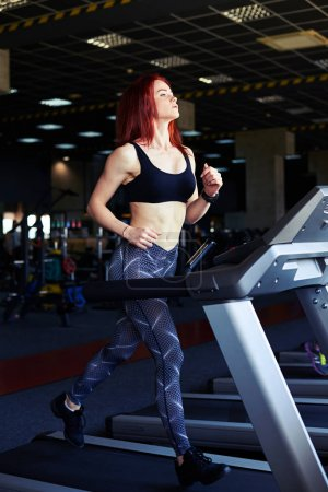 Pretty slim girl working out in a treadmill at the gym and smili