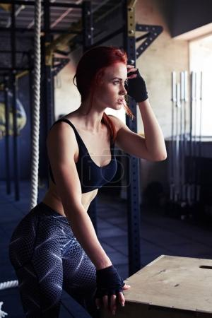 Female taking a break from endurance workout in gym