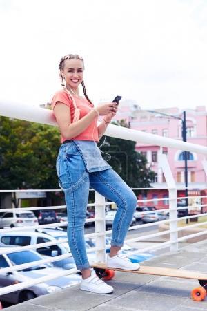 Young girl in headphones using smartphone
