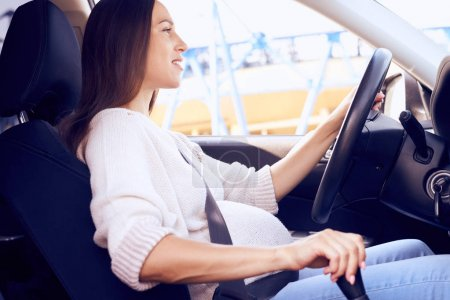 Smiling pregnant woman driving car
