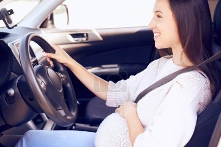 Happy pregnant woman with hand on wheel driving car