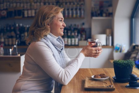 Affectionate mature woman sitting in cafe with cup of tea
