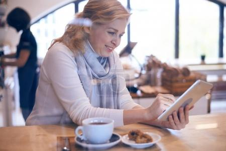 Casual mature woman working on tablet in cafe