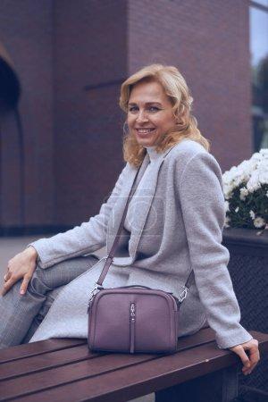 Stylish mature woman sitting on the bench