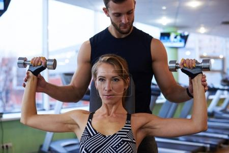 Young determined woman flexing biceps with personal trainer in g