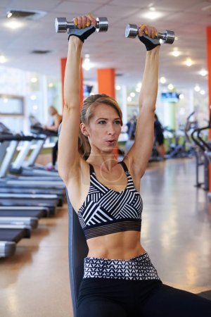 Sporty woman raising up dumbbells at gym