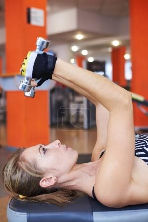 Woman lifting dumbbells while doing workout