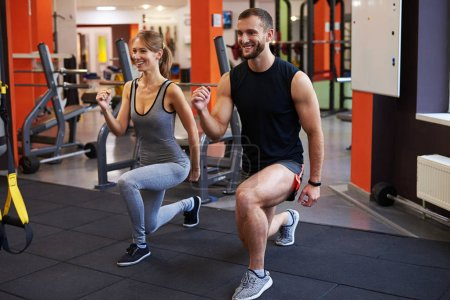 Athlete woman with personal trainer doing squats at gym