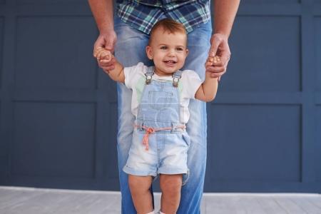 Petite fille faisant ses premiers pas avec le père