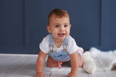 Cute blue-eyed baby girl crawling on the floor