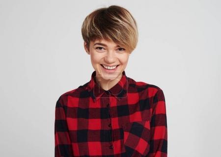 Young woman in checked shirt posing at camera