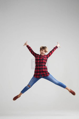 Positive woman jumping in excitement at studio