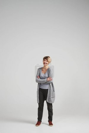 Smiling woman in cardigan folded arms