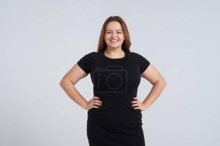 Happy woman in black dress posing at camera
