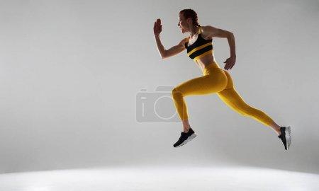 Photo pour Photo d'une sportive grossière courant en studio - image libre de droit