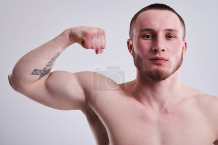 Closeup of young man showing his bicep