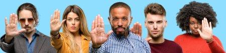 Grupo de personas mixtas, mujeres y hombres molestos con mala actitud haciendo señal de stop con la mano, diciendo no, expresando seguridad, defensa o restricción, tal vez empujando
