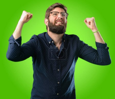 Young hipster man with big beard happy and excited celebrating victory expressing big success, power, energy and positive emotions. Celebrates new job joyful over green background