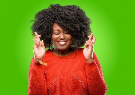 Beautiful african woman with crossed fingers asking for good luck
