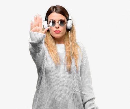 Photo pour Jeune femme écouter de la musique avec casque ennuyé avec une mauvaise attitude faire stop signe avec la main, dire non, exprimer la sécurité, la défense ou la restriction, peut-être pousser - image libre de droit