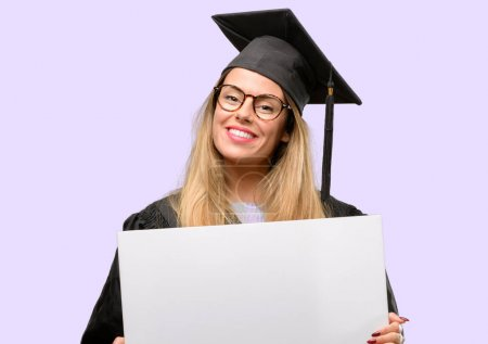 Young woman university graduate student holding blank advertising banner, good poster for ad, offer or announcement, big paper billboard