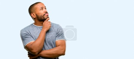 African american man with beard thinking and looking up expressing doubt and wonder isolated over blue background