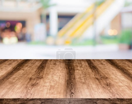 Wooden empty table board in front of blurred background. Can be