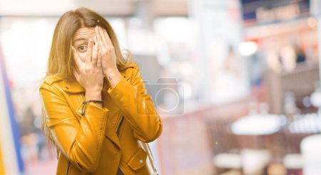 Beautiful young woman smiling having shy look peeking through her fingers, covering face with hands looking confusedly broadly at restaurant