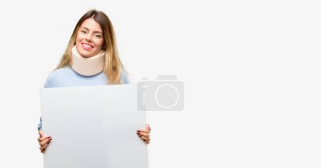 Young injured woman wearing neck brace collar holding blank advertising banner, good poster for ad, offer or announcement, big paper billboard
