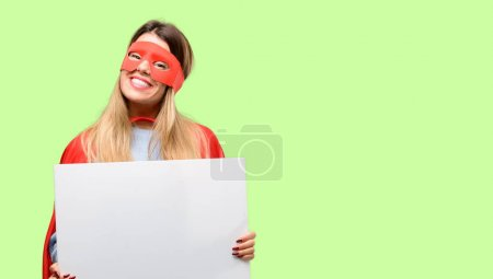 Young super woman holding blank advertising banner, good poster for ad, offer or announcement, big paper billboard