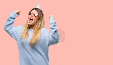 Photo for Young woman celebrates birthday happy and excited celebrating victory expressing big success, power, energy and positive emotions. Celebrates new job joyful - Royalty Free Image
