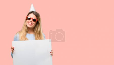 Young woman celebrates birthday holding blank advertising banner, good poster for ad, offer or announcement, big paper billboard