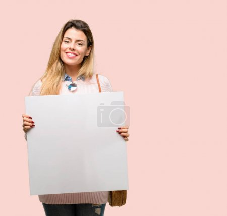 Young trendy woman holding blank advertising banner, good poster for ad, offer or announcement, big paper billboard