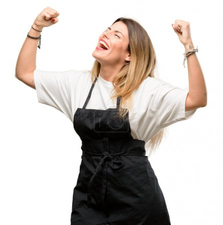 Shop owner woman wearing apron happy and excited celebrating victory expressing big success, power, energy and positive emotions. Celebrates new job joyful