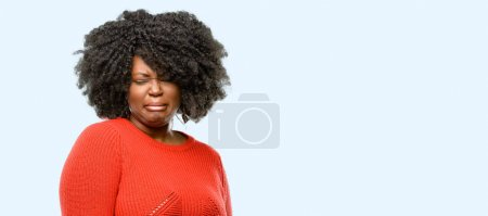 Photo for Beautiful african woman crying depressed full of sadness expressing sad emotion, blue background - Royalty Free Image